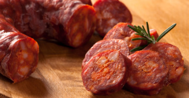 Spanish chorizo sausage with rosemary on rustic board